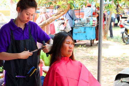 prettify: NACHUAK, MAHASARAKHAM - MARCH 21 : The unidentified barber is cutting an old woman hair in public secter services mobile project on March 21, 2012 at Nong Bua Daeng school court, Nachuak, Mahasarakham, Thailand.