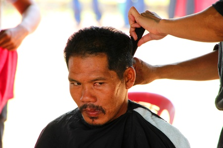 prettify: NACHUAK, MAHASARAKHAM - MARCH 21 : The unidentified barber is cutting an old man hair in public secter services mobile project on March 21, 2012 at Nong Bua Daeng school court, Nachuak, Mahasarakham, Thailand. Editorial