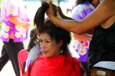 prettify: NACHUAK, MAHASARAKHAM - MARCH 21 : The unidentified barber is cutting a woman hair in public secter services mobile project on March 21, 2012 at Nong Bua Daeng school court, Nachuak, Mahasarakham, Thailand.
