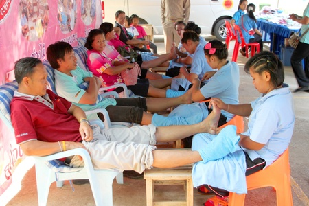NACHUAK, MAHASARAKHAM - MARCH 21 : The unidentified women are feet massaging spa treatment in public secter free services on March 21, 2012 at Nong Bua Daeng school, Nachuak, Mahasarakham, Thailand. Stock Photo - 13257416