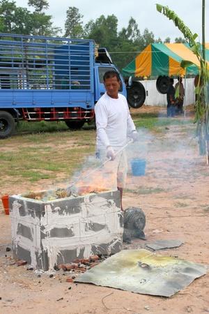 mahasarakham: NACHUAK, MAHASARAKHAM - APRIL 28 : Unidentified Buddhist is in ceremony of pouring liquid brass into Buddha mold on April 28, 2012 at Wat Hua Sra, Nachuak, Mahasarakham, Thailand.