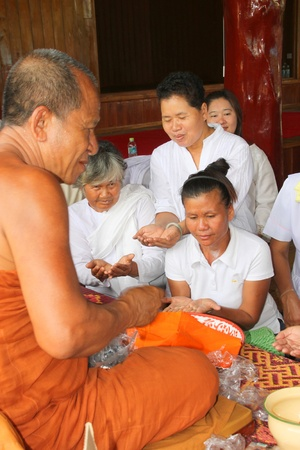 NACHUAK, MAHASARAKHAM - APRIL 28 : Unidentified Buddhists are given sacred objects by monk in ceremony of pouring liquid brass into Buddha mold on April 28, 2012 at Wat Hua Sra, Nachuak, Mahasarakham, Thailand. Stock Photo - 13365381