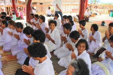 NACHUAK, MAHASARAKHAM - APRIL 28 : Unidentified Buddhists are making religious merit in ceremony of pouring liquid brass into Buddha mold on April 28, 2012 at Wat Hua Sra, Nachuak, Mahasarakham, Thailand. Stock Photo - 13365411