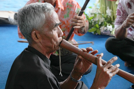 YANGSRISURAT, MAHASARAKHAM - MARCH 22 : Unidentified old man is performing traditional Thai grand orchestra in ordination ceremony on March 22, 2012 at Wat Nongbuasantu, Yangsrisurat, Mahasarakham, Thailand. Stock Photo - 13491265
