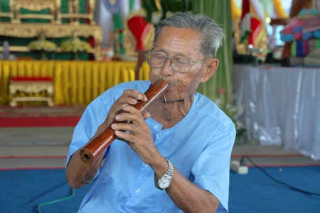welth: YANGSRISURAT, MAHASARAKHAM - MARCH 22 : Unidentified old man is performing traditional Thai grand orchestra in ordination ceremony on March 22, 2012 at Wat Nongbuasantu, Yangsrisurat, Mahasarakham, Thailand.