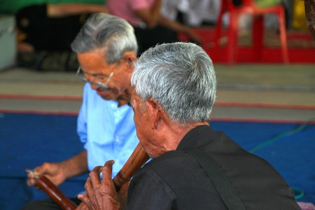 YANGSRISURAT, MAHASARAKHAM - MARCH 22 : Unidentified old men are performing traditional Thai grand orchestra in ordination ceremony on March 22, 2012 at Wat Nongbuasantu, Yangsrisurat, Mahasarakham, Thailand.