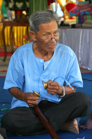 YANGSRISURAT, MAHASARAKHAM - MARCH 22 : Unidentified old man is performing traditional Thai grand orchestra in ordination ceremony on March 22, 2012 at Wat Nongbuasantu, Yangsrisurat, Mahasarakham, Thailand. Stock Photo - 13491256