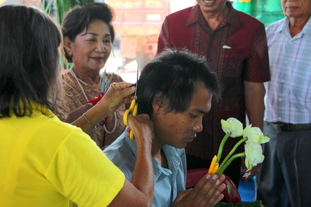 YANGSRISURAT, MAHASARAKHAM - MARCH 22 : Unidentified close relatives are cutting man hair in ordination ceremony on March 22, 2012 at Wat Nongbuasantu, Yangsrisurat, Mahasarakham, Thailand. Stock Photo - 13491301