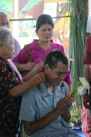 YANGSRISURAT, MAHASARAKHAM - MARCH 22 : Unidentified close relative is cutting man hair in ordination ceremony on March 22, 2012 at Wat Nongbuasantu, Yangsrisurat, Mahasarakham, Thailand. Stock Photo - 13491295