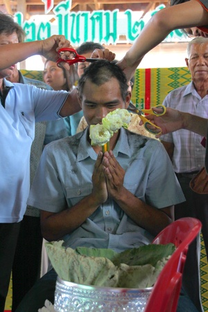 YANGSRISURAT, MAHASARAKHAM - MARCH 22 : Unidentified close relatives are cutting man hair in ordination ceremony on March 22, 2012 at Wat Nongbuasantu, Yangsrisurat, Mahasarakham, Thailand. Stock Photo - 13491300