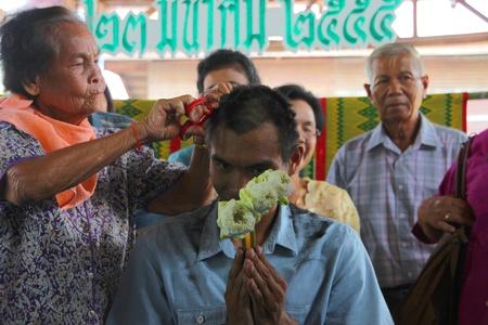 YANGSRISURAT, MAHASARAKHAM - MARCH 22 : Unidentified close relative is cutting man hair in ordination ceremony on March 22, 2012 at Wat Nongbuasantu, Yangsrisurat, Mahasarakham, Thailand. Stock Photo - 13491303