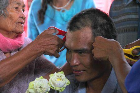 YANGSRISURAT, MAHASARAKHAM - MARCH 22 : Unidentified close relatives are cutting man hair in ordination ceremony on March 22, 2012 at Wat Nongbuasantu, Yangsrisurat, Mahasarakham, Thailand. Stock Photo - 13491314