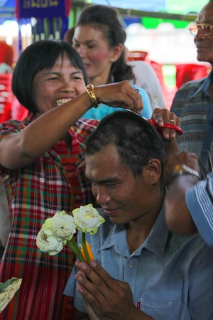 YANGSRISURAT, MAHASARAKHAM - MARCH 22 : Unidentified close relatives are cutting man hair in ordination ceremony on March 22, 2012 at Wat Nongbuasantu, Yangsrisurat, Mahasarakham, Thailand. Stock Photo - 13491293