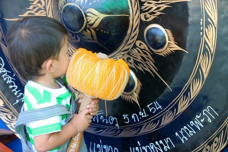YANGSRISURAT, MAHASARAKHAM - MARCH 22 : Unidentified child is hitting gong in ordination ceremony on March 22, 2012 at Wat Nongbuasantu, Yangsrisurat, Mahasarakham, Thailand. Stock Photo - 13491317