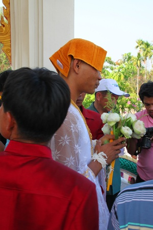 kinfolk: YANGSRISURAT, MAHASARAKHAM - MARCH 22 : Unidentified man in naga clothes and in ordination ceremony is coming into temple on March 22, 2012 at Wat Nongbuasantu, Yangsrisurat, Mahasarakham, Thailand.