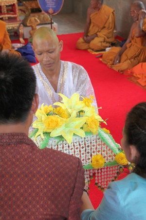 YANGSRISURAT, MAHASARAKHAM - MARCH 22 : Unidentified man in naga clothes is given Buddhist clothes from his parents on March 22, 2012 at Wat Nongbuasantu, Yangsrisurat, Mahasarakham, Thailand. Stock Photo - 13491294