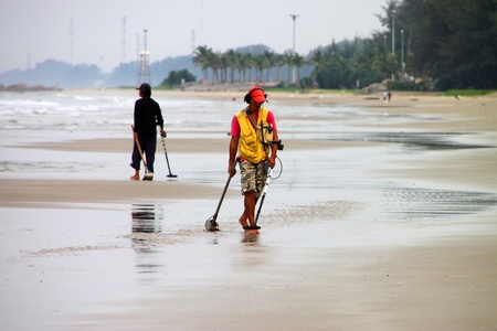 BAN PHE, RAYONG - MAY 10 : Unidentified men are cleaning the sand beach on May 10, 2012 at Ban Phe sea shore, Rayong, Thailand. Editorial