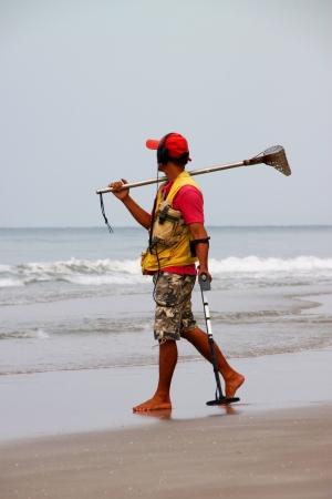 BAN PHE, RAYONG - MAY 10 : Unidentified man is cleaning the sand beach on May 10, 2012 at Ban Phe sea shore, Rayong, Thailand.