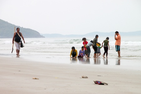 BAN PHE, RAYONG - MAY 10 : Unidentified man is cleaning sand beach while tourists are playing on May 10, 2012 at Ban Phe sea shore, Rayong, Thailand.