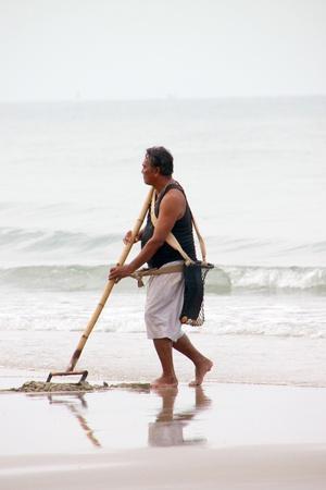 BAN PHE, RAYONG - MAY 10 : Unidentified man is cleaning the sand beach on May 10, 2012 at Ban Phe sea shore, Rayong, Thailand. Stock Photo - 13668875