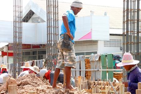 coolie hat: MUANG, BURIRAM - JUNE 9 : Unidentified men are working in the building site on June 9, 2012 at Taweekit Plaza, Muang, Buriram, Thailand. Editorial