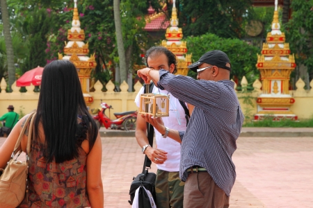 PHRA THART LAUNG, VIENTIANE - MAY 21 : Unidentified tourists are making religious merit by set birds free on May 21, 2012 at Phra Thart Laung, Vientiane, Lao P.D.R.