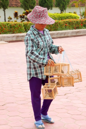 PHRA THART LAUNG, VIENTIANE - MAY 21 : Unidentified woman is selling birds for some tourists may set them free on May 21, 2012 at Phra Thart Laung, Vientiane, Lao P.D.R.