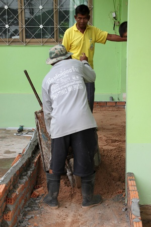 coolie hat: NACHUAK, MAHASARAKHAM - JUNE 14 : Unidentified men are working in the building site on June 14, 2012 at Nachuak district hall, Mahasarakham, Thailand.