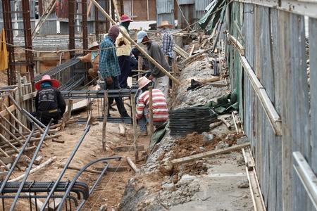 coolie hat: MUANG, BURIRAM - JUNE 16 : Unidentified men are working in the building site on June 16, 2012 at Taweekit Plaza, Muang, Buriram, Thailand.