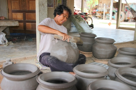 MUANG, MAHASARAKHAM - JUNE 12 : Unidentified woman is molding earthenware pots on June 12, 2012 at Ban Moh (Pottery village), Muang, Mahasarakham, Thailand.