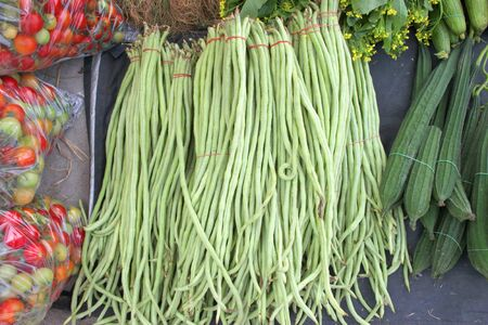 Cow-pea in piles of fruits and vegetables photo