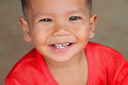 credulous: MUANG, MAHASARAKHAM - JUNE 29 : Unidentified boy is smiling while looking at camera on June 29, 2012 at Ban Moh (Pottery village), Muang, Mahasarakham, Thailand.