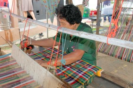 MUANG, MAHASARAKHAM - JUNE 11 : Unidentified woman is showing traditional textile weaving on June 11, 2012 at Don Tum village plaza, Muang, Mahasarakham, Thailand.