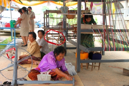 MUANG, MAHASARAKHAM - JUNE 11 : Unidentified women are showing traditional textile weaving on June 11, 2012 at Don Tum village plaza, Muang, Mahasarakham, Thailand.