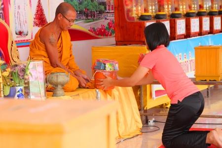 NA DUN, MAHASARAKHAM - JULY 15 : The unidentified Buddhist is making religious merit as usual on July 15, 2012 at Na Dun Pagoda, Mahasarakham, Thailand. Editorial