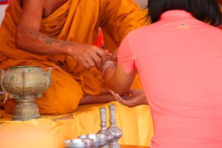 mahasarakham: NA DUN, MAHASARAKHAM - JULY 15 : The unidentified Buddhist monk is putting holy thread on woman wrist on July 15, 2012 at Na Dun Pagoda, Mahasarakham, Thailand.