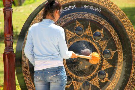 mahasarakham: NA DUN, MAHASARAKHAM - JULY 15 : The unidentified Buddhist is hitting a gong in making religious merit on July 15, 2012 at Na Dun Pagoda, Mahasarakham, Thailand.