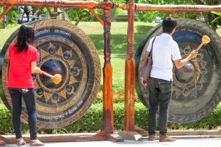 mahasarakham: NA DUN, MAHASARAKHAM - JULY 15 : The unidentified Buddhists are hitting a gong in making religious merit on July 15, 2012 at Na Dun Pagoda, Mahasarakham, Thailand.