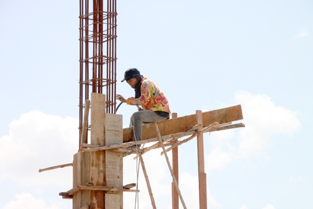 coolie hat: MUANG, BURIRAM - JULY 21 : Unidentified man is working in the building site on July 21, 2012 at Taweekit Plaza, Muang, Buriram, Thailand. Editorial