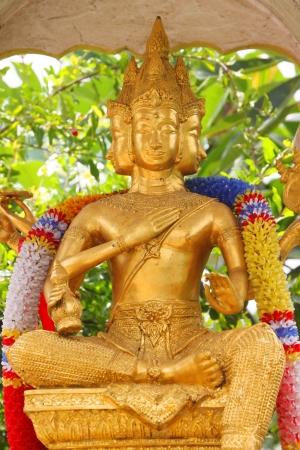 Four faces and golden Brahma statue photo