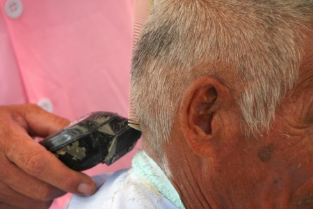 Hair cutting, hair stylist at work with scissors, comb and electric hair clipper photo