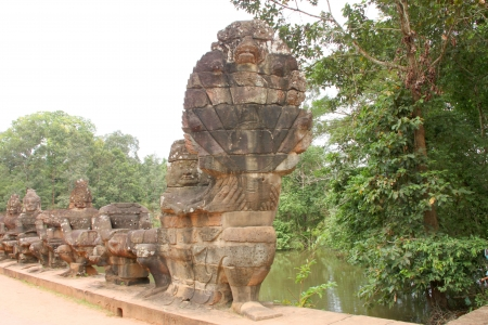 Naga statue on the bridge at entrance of Angkor Thom, Siamreap, Khmer Republic photo