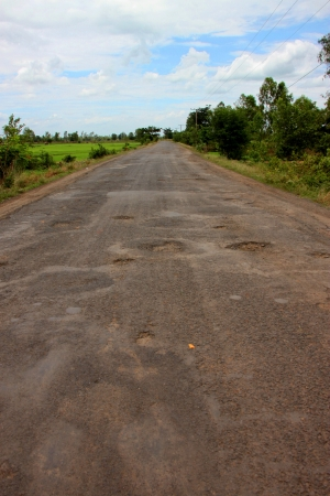Broken, damaged and cracked road in local motorway and rice field photo