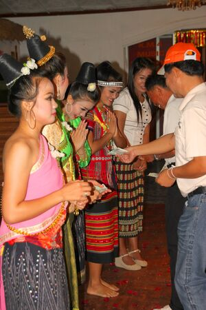 VIENTIANE, LAO P.D.R. - MAY 21 : Unidentified tourists are giving money reward to group of Lao dancers on May 21, 2012 at KM 4 Riverside Restaurant - Karaoke, Vientiane, Lao P.D.R.