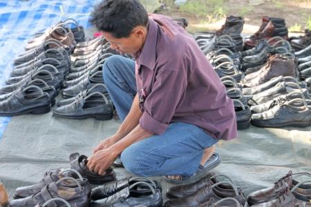 comprando zapatos: MUANG, MAHASARAKHAM - 14 DE JULIO: El cliente no identificado es la compra de los zapatos de los vendedores ambulantes el 14 de julio de 2012 a la ciudad plaza, Muang, Mahasarakham, Tailandia.