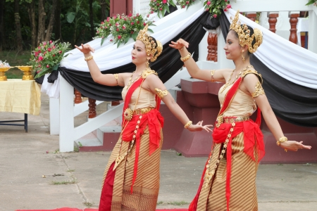 MUANG, MAHASARAKHAM - AUGUST 22 : Unidentified women are performing Thai dance in funeral on August 22, 2012 at Wat Aphisit, Muang, Mahasarakham, Thailand.