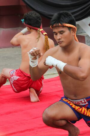 MUANG, MAHASARAKHAM - AUGUST 22 : Unidentified men are performing Thai boxing show in funeral on August 22, 2012 at Wat Aphisit, Muang, Mahasarakham, Thailand.