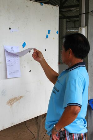 MUANG, MAHASARAKHAM - AUGUST 28 : Unidentified voter is checking village headman result votes on August 28, 2012 at village hall, Ban Dong Noi, Wang Nang, Muang, Mahasarakham, Thailand.