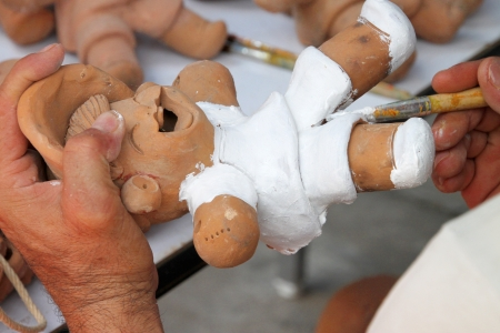 hands of potter, painting an earthen doll white color photo