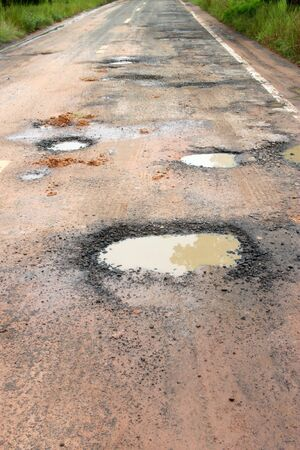 Broken, damaged and cracked road in local motorway because of heavy rain and overloaded trucks photo